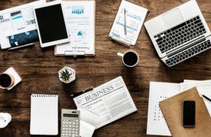 immagine di una scrivania con fogli, giornali, una piantina, una calcolatrice, delle penne, un tablet e dei caffè per rappresentare un ambiente di lavoro